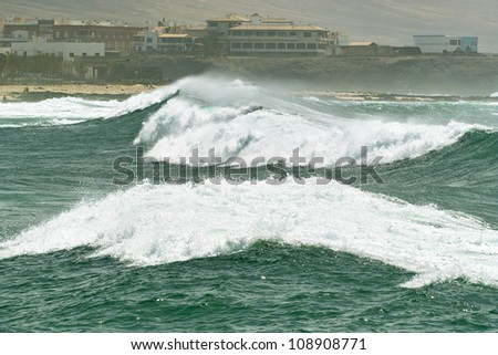 Big roller ocean wave with white foam running along the tropical island beach - stock photo