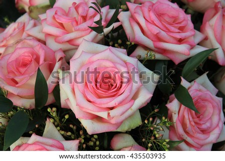 Big roses in different shades of pink as part of a floral arrangement - stock photo
