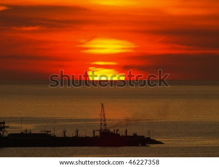 Big round sunset hiding behind the clouds over the horizon on Gulf of Mexico (from Mexico Campache) with silhouette of a big ship