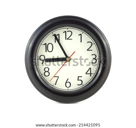 Big round wall clock, with a dark rim on a white background close-up and arrows showing five minutes to nine o'clock - stock photo