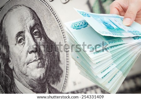 big Russian money against hundred dollar bill - concept of Russian rouble collapse - stock photo