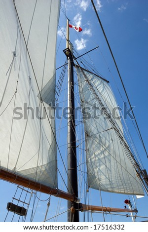 Big sail and Canadian flag on blue sky background
