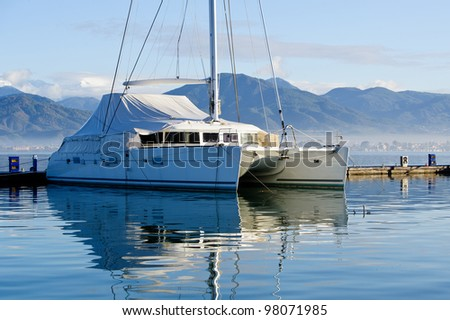 Big sailing catamaran moored. Mountain ladscape and wave breaking pier. - stock photo