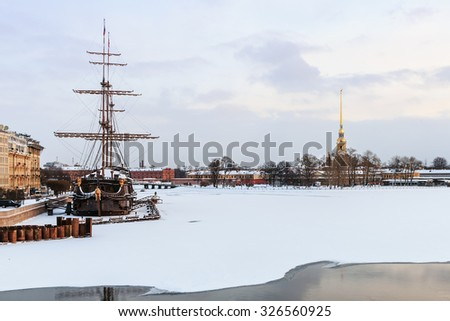 big sailing-ship at the harbor in winter, st.petersburg against the backdrop of the fortress, russia. Focus on boat - stock photo