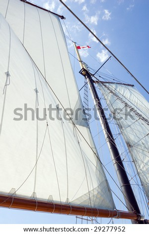 Big sails and masts on blue sky background