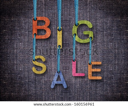 Big sale letters hanging strings with blue sackcloth background. - stock photo