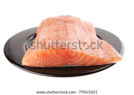 big salmon chunk on black plate over white