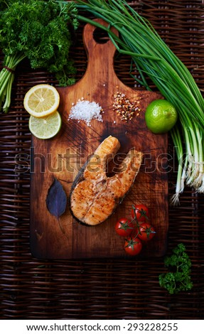 Big salmon steak baked in the oven until golden brown lying on a wooden surface, for serving fish perfect tomatoes chives and lemon, cook restaurant cooked piece of salmon on the grill - stock photo