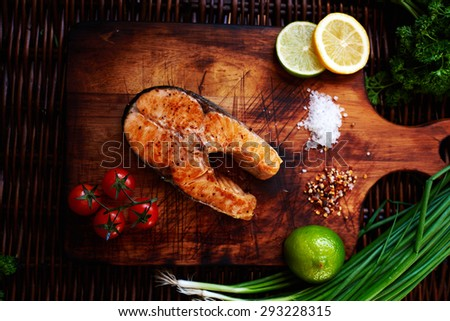 Big salmon steak cooking at home, watered lemon, served it with a salad of fresh tomatoes, Fuming just pulling out of the oven a piece of salmon - stock photo