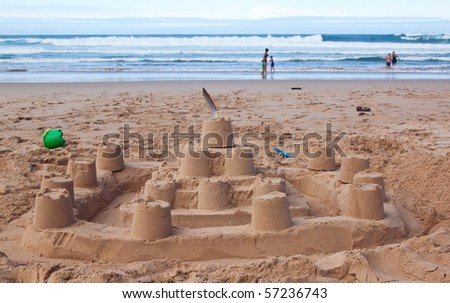 Big sandcastle on the beach with people playing in the surf - stock photo
