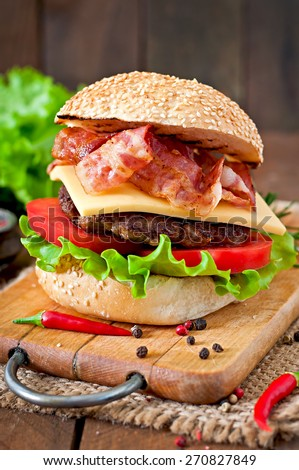 Big sandwich - hamburger burger with beef, cheese, tomato and fried bacon - stock photo