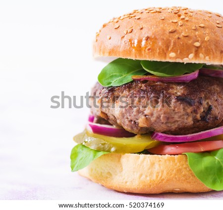 Big sandwich - hamburger burger with beef, pickles, tomato and red onions on light background.