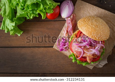 Big sandwich - hamburger burger with beef, red onion, tomato and fried bacon. Top view - stock photo