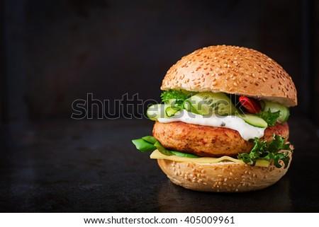 Big sandwich - hamburger with juicy chicken burger, cheese, cucumber, chili and tartar sauce on black background - stock photo