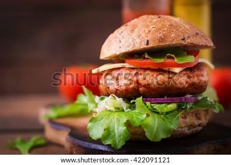 Big sandwich - hamburger with juicy chicken burger, cheese, tomato, and red onion on wooden background - stock photo
