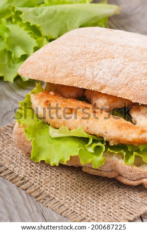 Big sandwich with chicken nuggets, lettuce on a wooden background