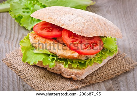 Big sandwich with chicken nuggets, tomato and lettuce on a wooden background - stock photo