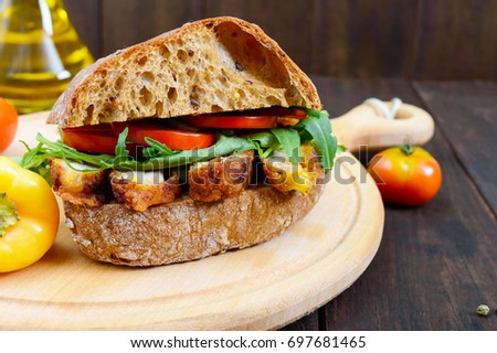 Big sandwich with pieces of meat, arugula, tomato, cereal ciabatta on a cutting board on a dark wooden background.