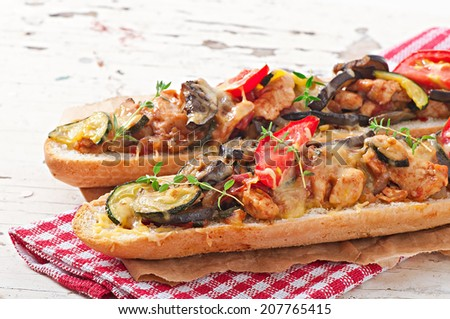 Big sandwich with roasted vegetables (zucchini, eggplant, tomatoes) with cheese and thyme on old wooden background - stock photo