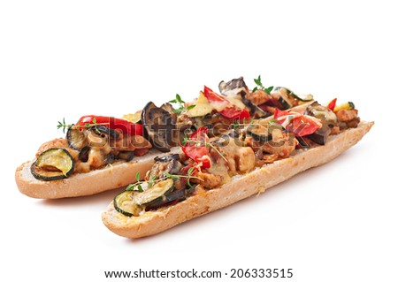 Big sandwich with roasted vegetables (zucchini, eggplant, tomatoes) with cheese and thyme on white background - stock photo