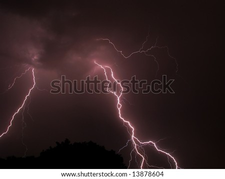 Big scary lightning storm on a stormy night with tree in foreground - stock photo