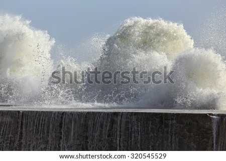 Big sea wave against pier of a river mouth harbor from the north of Portugal - stock photo