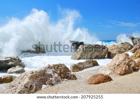 Big sea wave splashing over the shore rocks with a high sea spray - stock photo