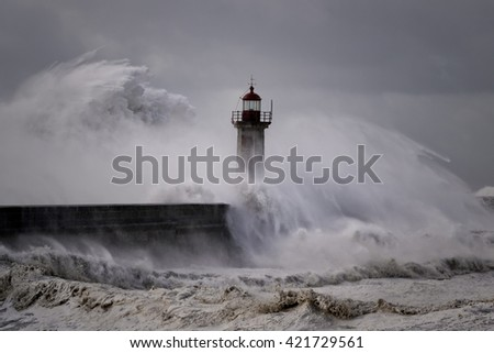 Big sea waves over Oporto old Lighthouse, Douro river mouth, in a stormy morning with cyclonic winds. - stock photo