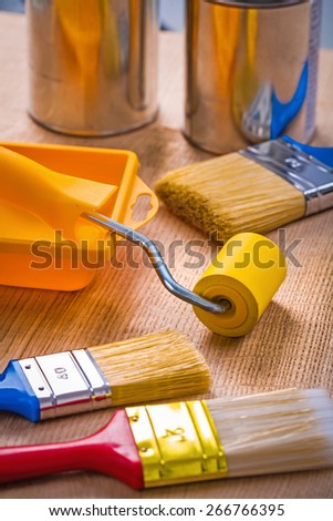big set of painting tools on wooden board paint brushes roller tray cans  - stock photo