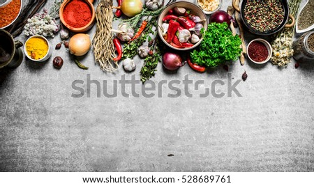 Big set of spices and herbs. On a stone background.