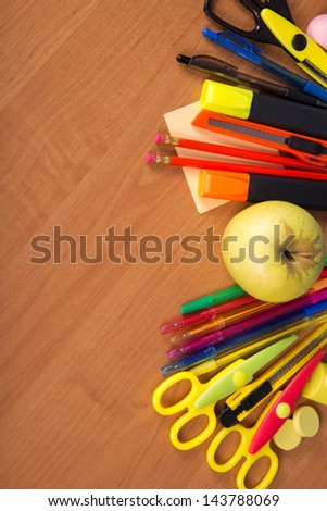 Big set of the bright office tools and apple, which have been beautifully laid on a table