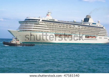 Big ship arrival with tugboat. - stock photo