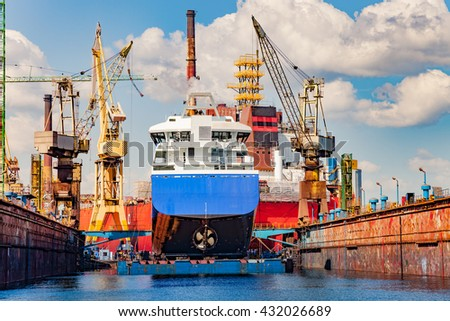 Big ship under repairing on floating dry dock in shipyard. - stock photo