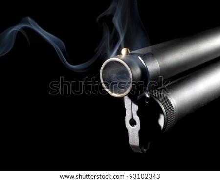 Big shotgun that has blue smoke coming from its barrel - stock photo