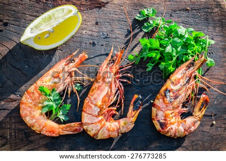 Big shrimps with lemon and parsley served in garden - stock photo