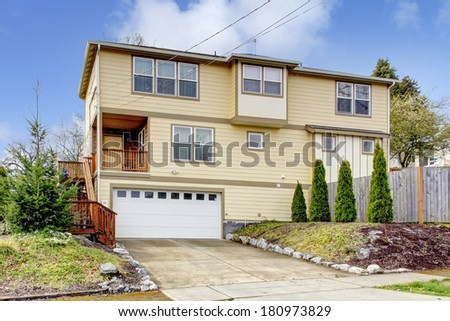 Big siding house. View of the drive way, front porch, deck with stairs - stock photo