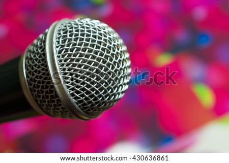 Big silver microphone in concert hall with defocused bokeh lights on background - stock photo