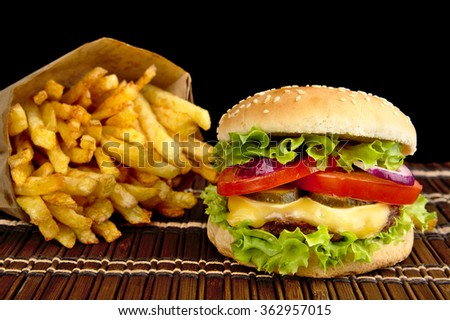 Big single cheeseburger with french fries on wooden mat on black background