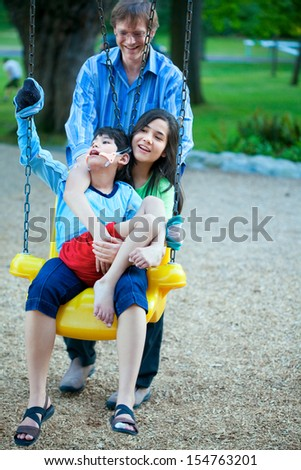 Big sister holding disabled brother on special needs swing at playground in park as father pushes. Child has cerebral palsy. - stock photo