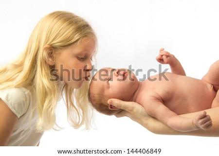 Big sister kisses new little sister - stock photo