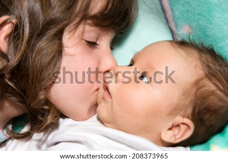 Big sister kissing her brother - stock photo