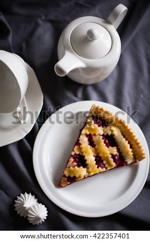 Big slice of cherry pie on a plate with teapot - stock photo