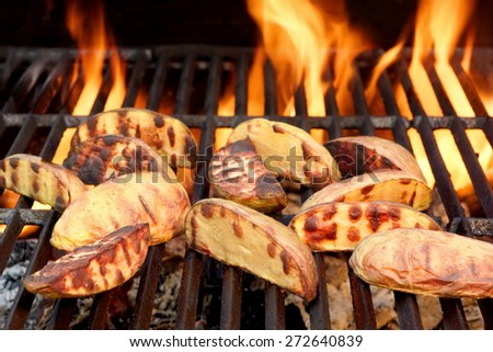 Big Slice Of Village-Style Potatoes On Hot BBQ Charcoal Grill. Flames of Fire In The Background. Tasty Snack For Outdoor Summer Barbecue Party Or Picnic. - stock photo