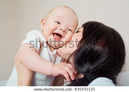 Big smile toddler. Mom hugging baby. Kid laughing in the arms of the mother, much laughing. The concept of a happy family. - stock photo