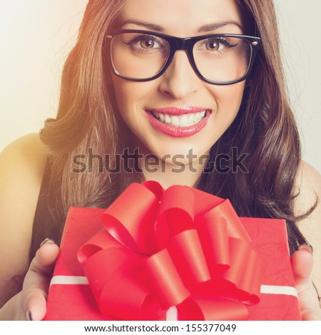 Big smile young Caucasian woman with red present wearing eyeglasses looking at camera - stock photo