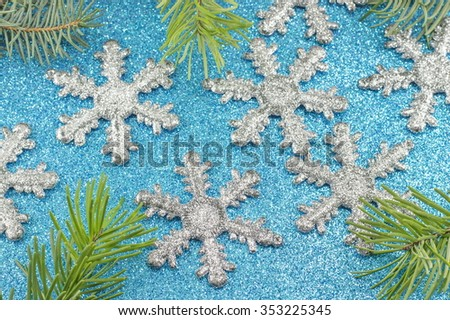 Big snowflakes and fir tree on blue background - stock photo
