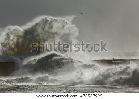 Big splash from storm waves breaking over rocks and pier