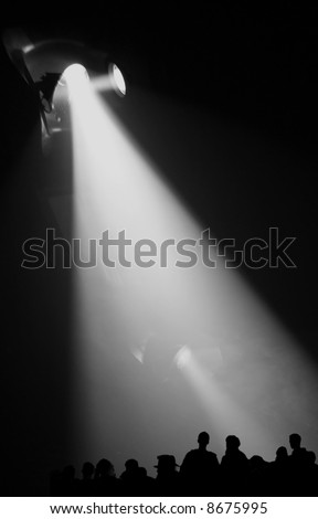 Big spotlight on people / audience silhouettes at a concert - stock photo