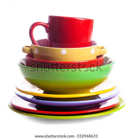 Big stack of different colors mugs and plate on white background, one above the another