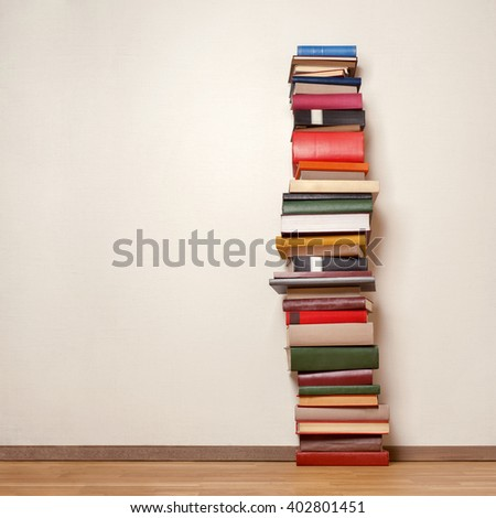 Big stack of old books on wooden floor - stock photo